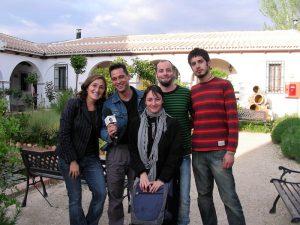 La directora del hotel, Ángela Jiménez Egea, posa sonriente sujetando el micrófono junto al presentador del programa Andalucía Directo, Jesús Toral y su equipo de cámaras y operadores. Detrás se ve el jardín del hotel con sus arcos blancos y su fuente de tinajas.