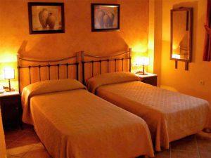 Habitación con dos camas independientes, paredes naranjas y apliques de tipo japonés, en líneas rectas y suaves. A la derecha, un coqueto espejo da a la estancia un toque acogedor.