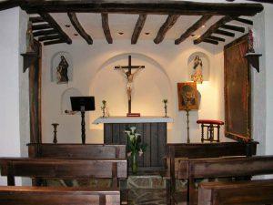 Oratorio con bancos (en la imagen se ven 6), en dos niveles. En el altar, un misal romano, y detrás el Cristo de la capilla flanqueado por las estatuas de la Virgen María y San José. A los lados del altar, un atril de madera y hermosos cuadros del siglo XVIII del Ecce Homo y San Francisco de Padua.