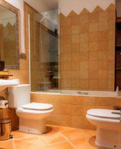Baño de habitación con bañera, lavabo cuadrado como en tiempos antiguos, azulejos rústicos en tonos tostados y preciosa cenefa en tonos azules y grises, imitando la cerámica antigua andaluza.