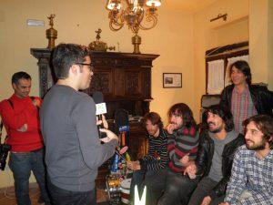 El reportero de La 2 televisión entrevista a la banda en el salón donde han grabado el disco. El periodista sostiene un micrófono con el logotipo de LA 2, y a su izquierda su compañero fotógrafo sonríe a los Lori.