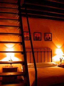 Preciosa habitación con paredes naranjas, tres simpáitcos cuadros de flores y cama con cabecero de varales de forja. En primer plano la escalera de madera de sube a la buhardilla del dormitorio.