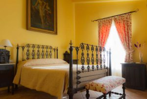 Señorial cama de forja de principios del siglo XX, con flores adornando sus patas. Sobre la cama un antiguo cuadro de temática mitológica, el baño de Diana. Al fondo un balcón con hermosas cortinas estampadas de beige y motivos burdeos.