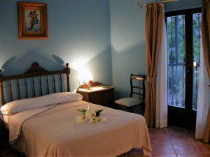 Habitación con paredes azules, y cama antigua con cabecero de varales de madera. Sobre la cama, el cuadro del Primo Baccio (el primer beso) del artista italiano Raphaelo.