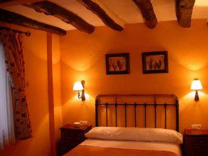 Castiza habitación con vigas de madera en el techo, pared naranja y dos cálidos apliques a los lados.