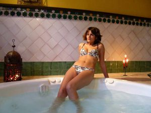 Mujer en bikini disfruta de las burbujas del jacuzzi de la sala de hidroterapia. La pared tiene alicatado de fajalauza de color blanco mármol, con cenefa de estrellas árabes como en la Alhambra. A los lados de la chica, farol árabe y vela que da a la sala un ambiente acogedor y relajante.