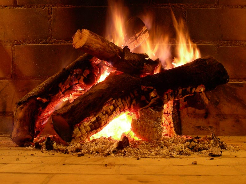 Leña ardiendo en la chimenea del salón del hotel