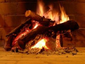 Detalle de la leña ardiendo en la chimenea del salón del hotel Huerta Nazarí