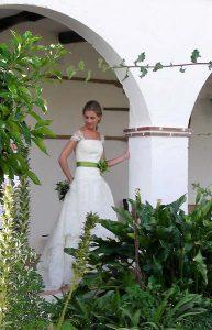 Novia junto a un arco del patio ajardinado