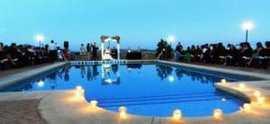Piscina del hotel Huerta Nazarí adornada con velas para una boda