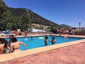 huéspedes disfrutando de la piscina en verano