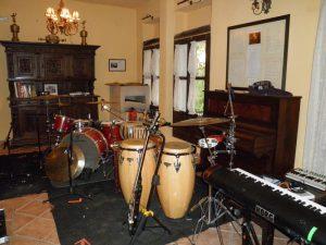 El salón del hotel está transformado en estudio de grabación. A la derecha se encuentran los teclados de Noni, en el centro los bongos de Alfredo y al fondo la batería con sus parabenes. Todo ello alrededor del piano y el aparador del salón.