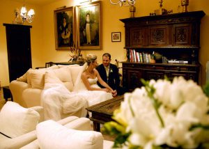 Detalle del acogedor salón con un gran sofá sobre el que se sientan una pareja de novios que se miran enamorados. Al fondo dos cuadros de un niño y una niña de estilo goyesco mejicano. El ramo de flores de la novia en primer plano, da frescura y color a la imagen.