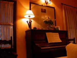 Hermoso piano con partituras, sobre el que se puede ver un cuadro homenaje al poeta granadino Javier Egea. Junto al cuadro, una lámpara imitación de quinqué antiguo y flores, y a la derecha un gran ventanal que da al jardín del hotel.